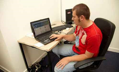 an autistic male service user sitting at a computer in Hamilton Lodge IT Suite