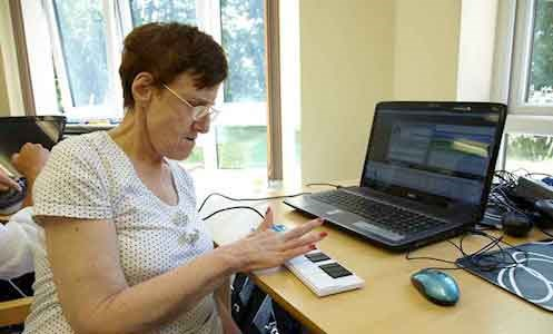 autistic female service user working at a computer in Hamilton Lodge's IT suite
