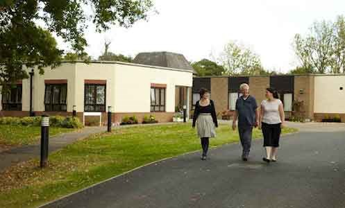 autistic male service user with two female support workers walking outside Hamilton Lodge