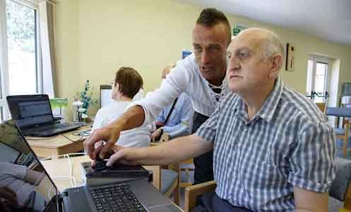 autistic male service user with  support worker in Hamilton Lodge's IT suite