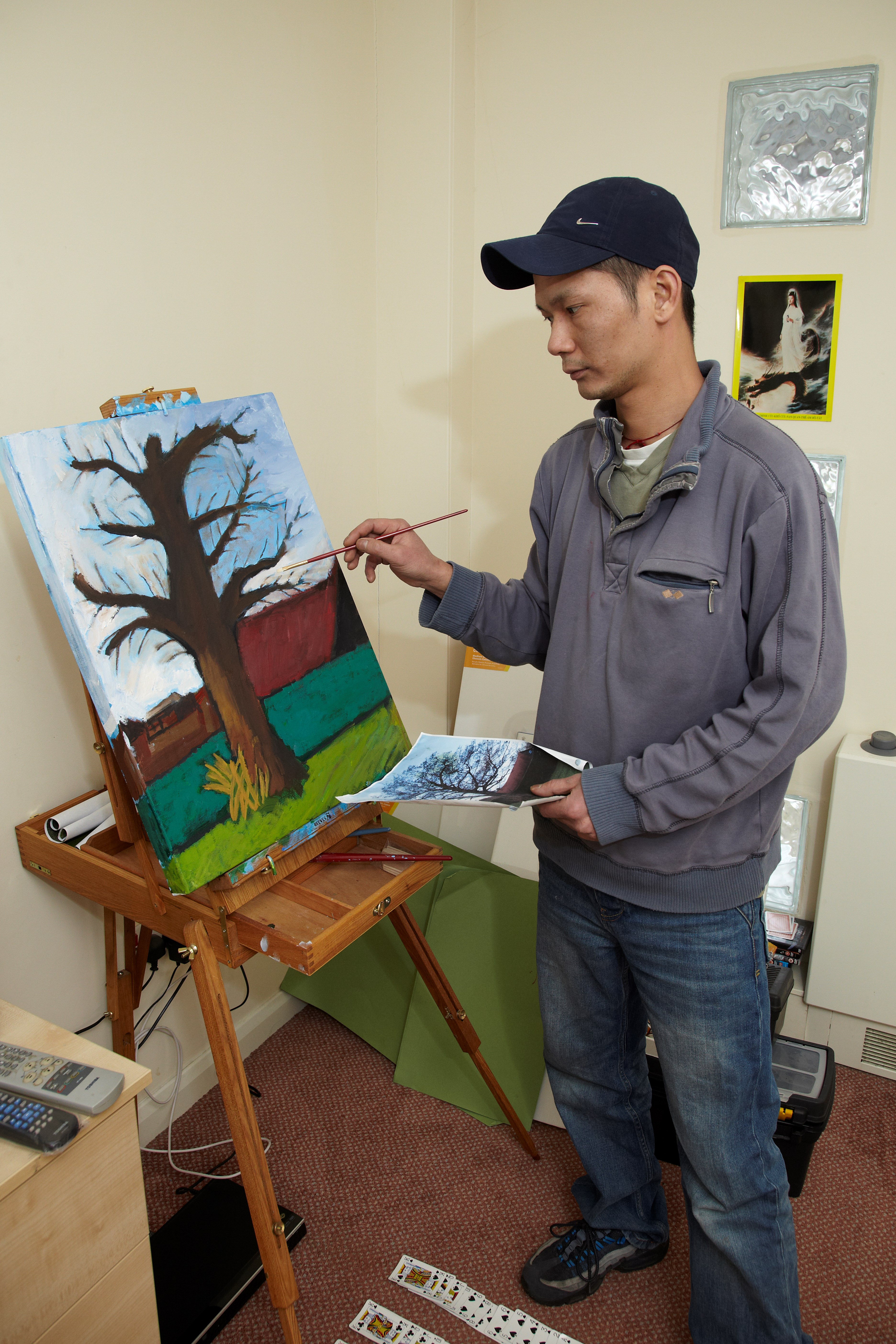 service user painting a picture of a tree in his room at Bristol Road