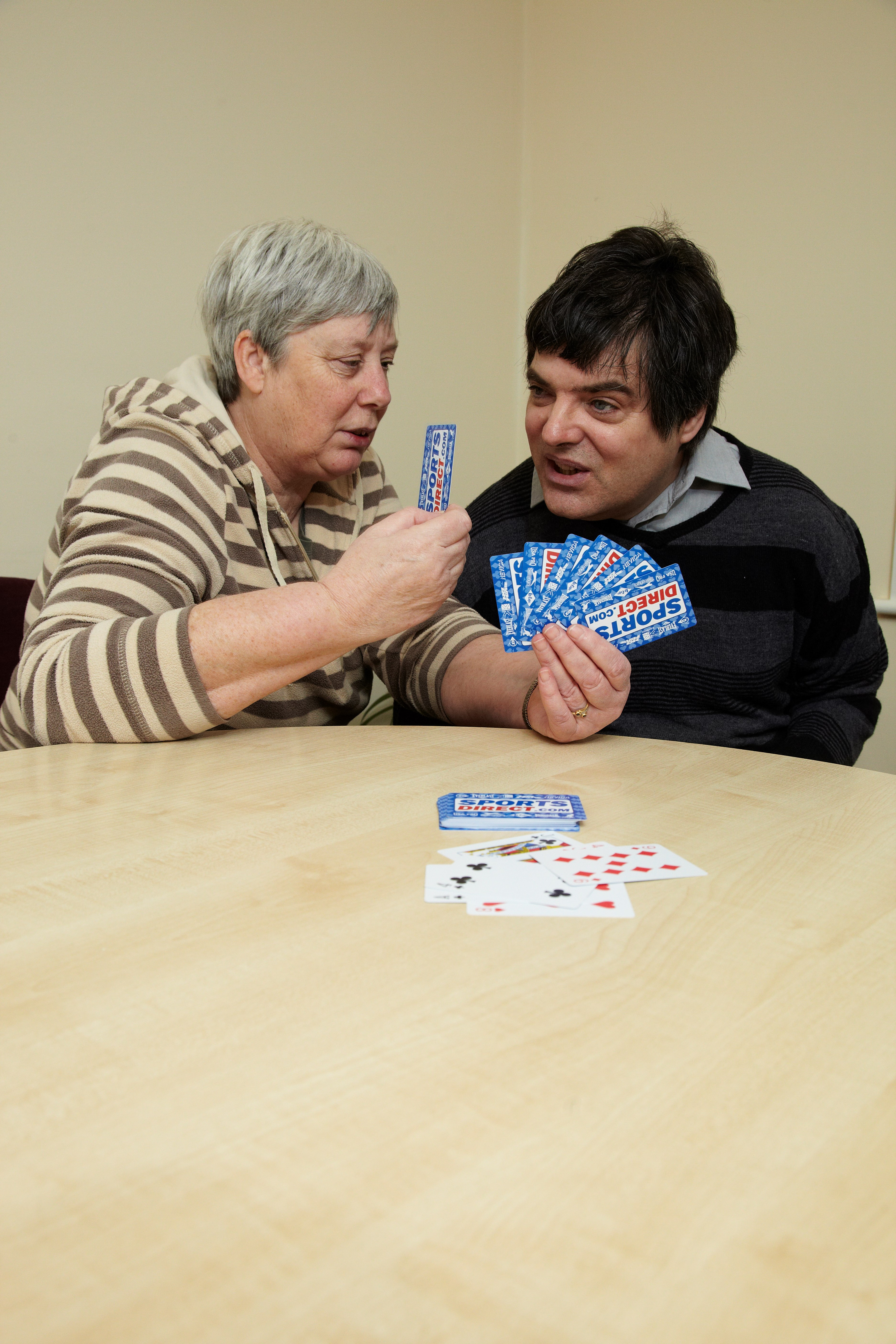 service user playing cards with support worker in the lounge at Bristol Road