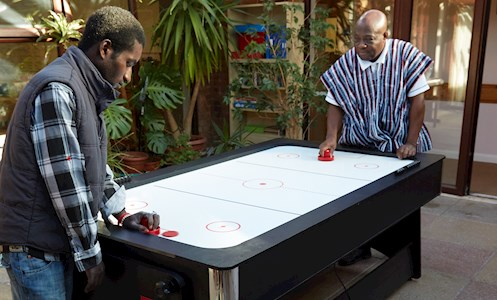 service users playing air hockey in the games room at TEM House
