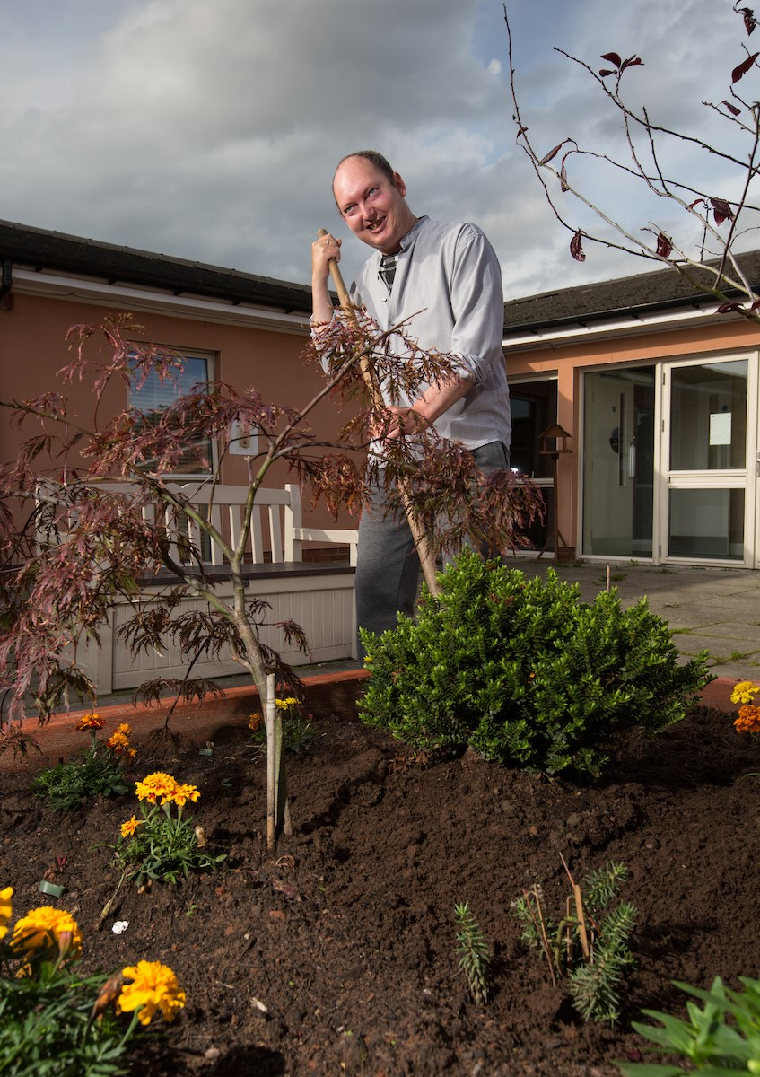 service user gardening in front of Graham Anderson House