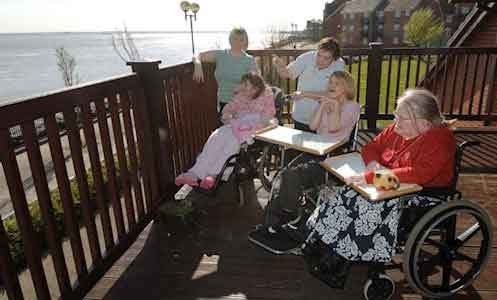 Service users sitting on the balcony over looking the sea at Victoria House
