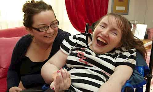 Female service user laughing with support worker in the lounge area at Victoria House