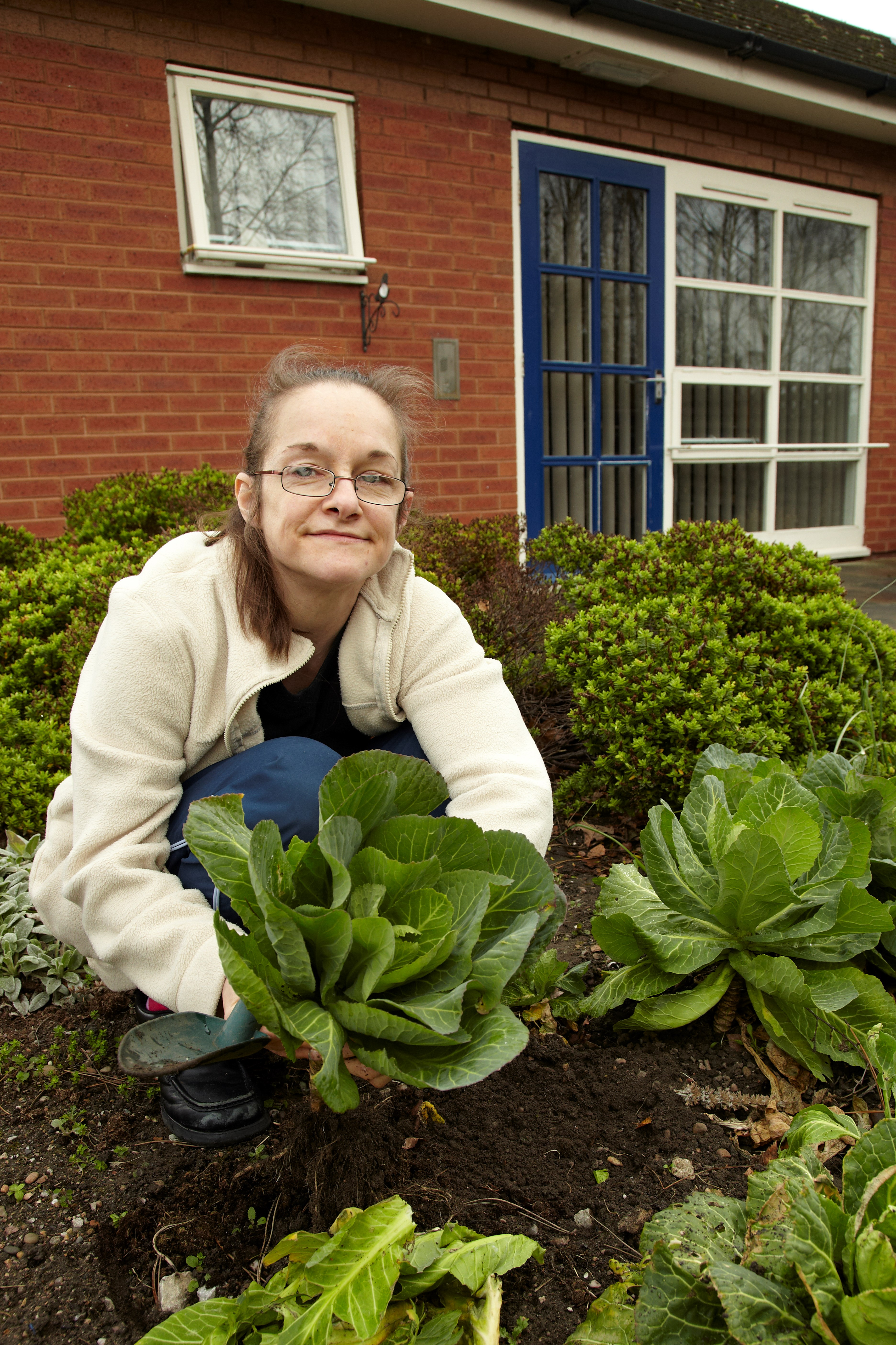 service user working in the garden outside Gregory Court