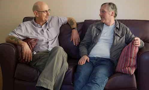 two male service users sit on the sofa in York House's lounge area