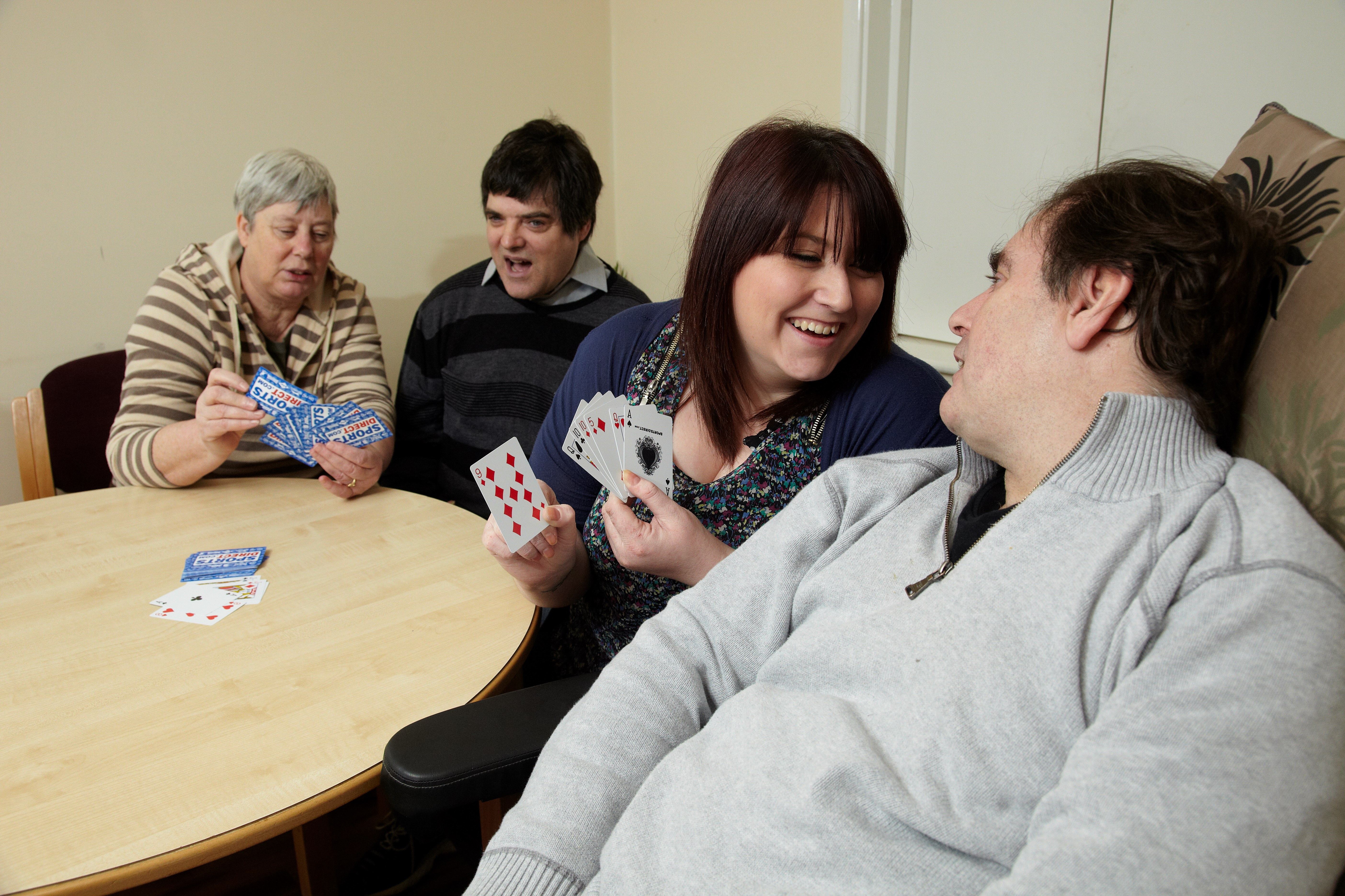service users and support workers playing games in the lounge at Bristol Road