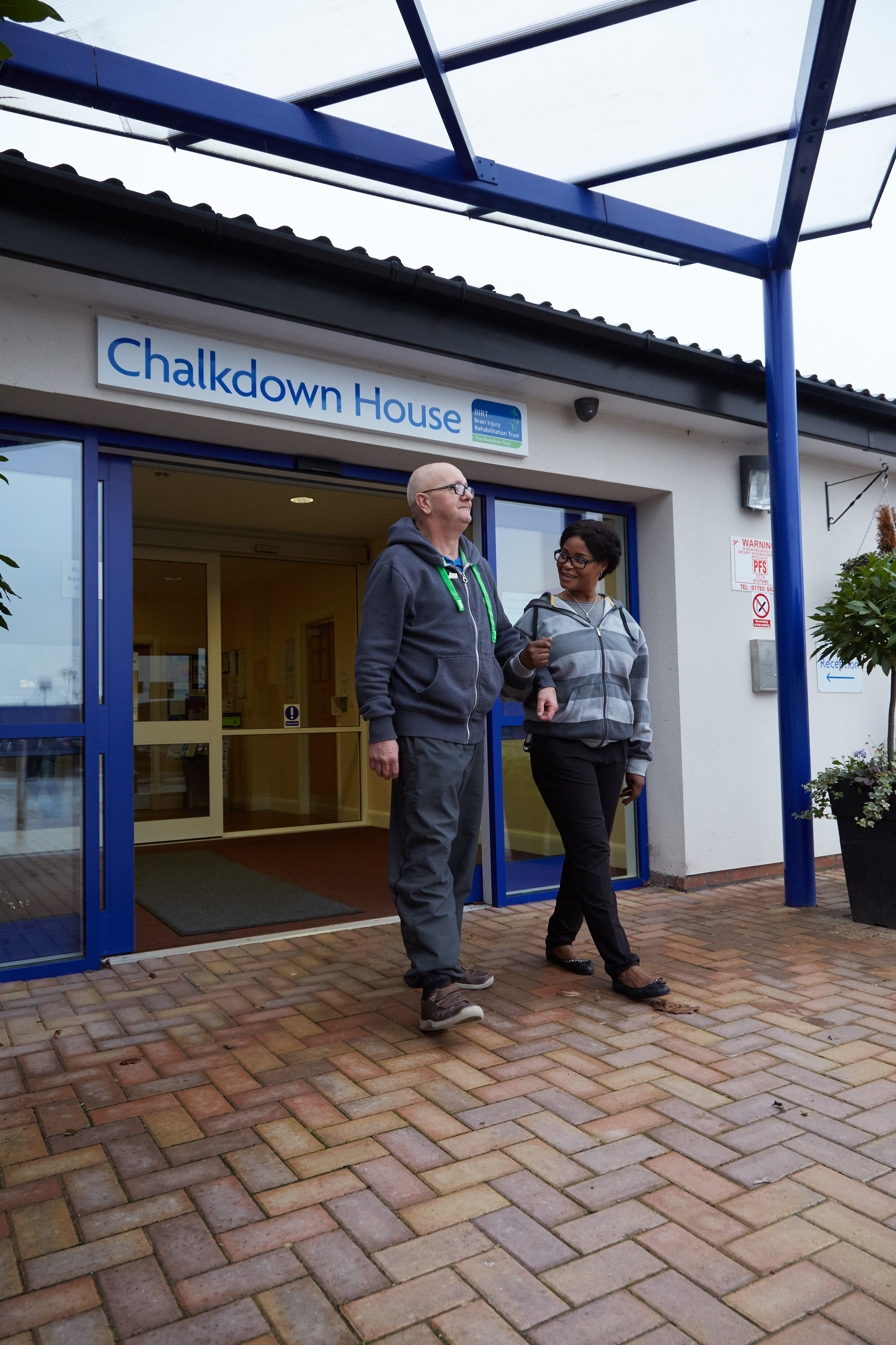 male service user standing outside Chalkdown House with female support worker