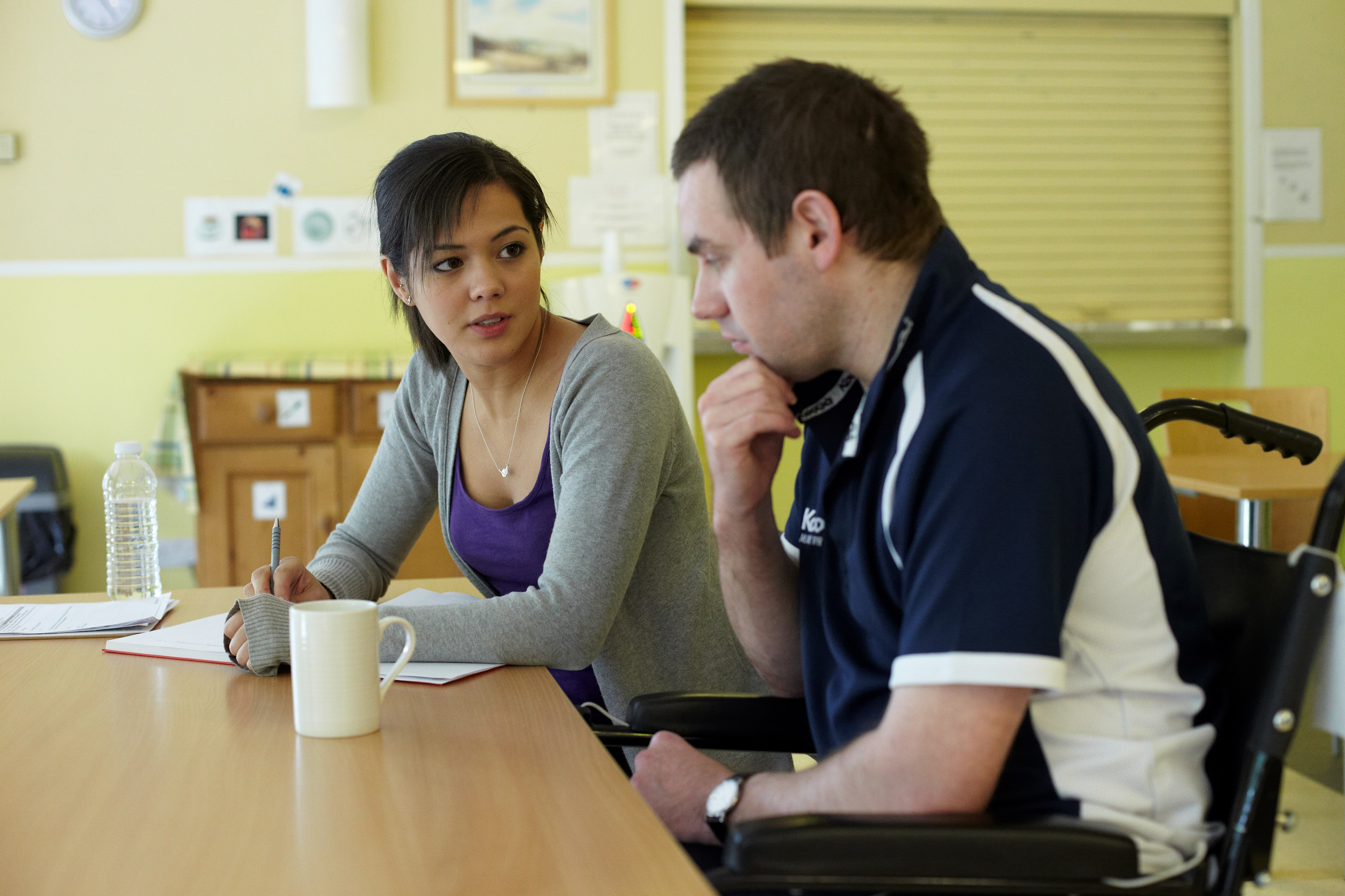 service user sitting with support worker in the recreation room at Daniel Yorath House