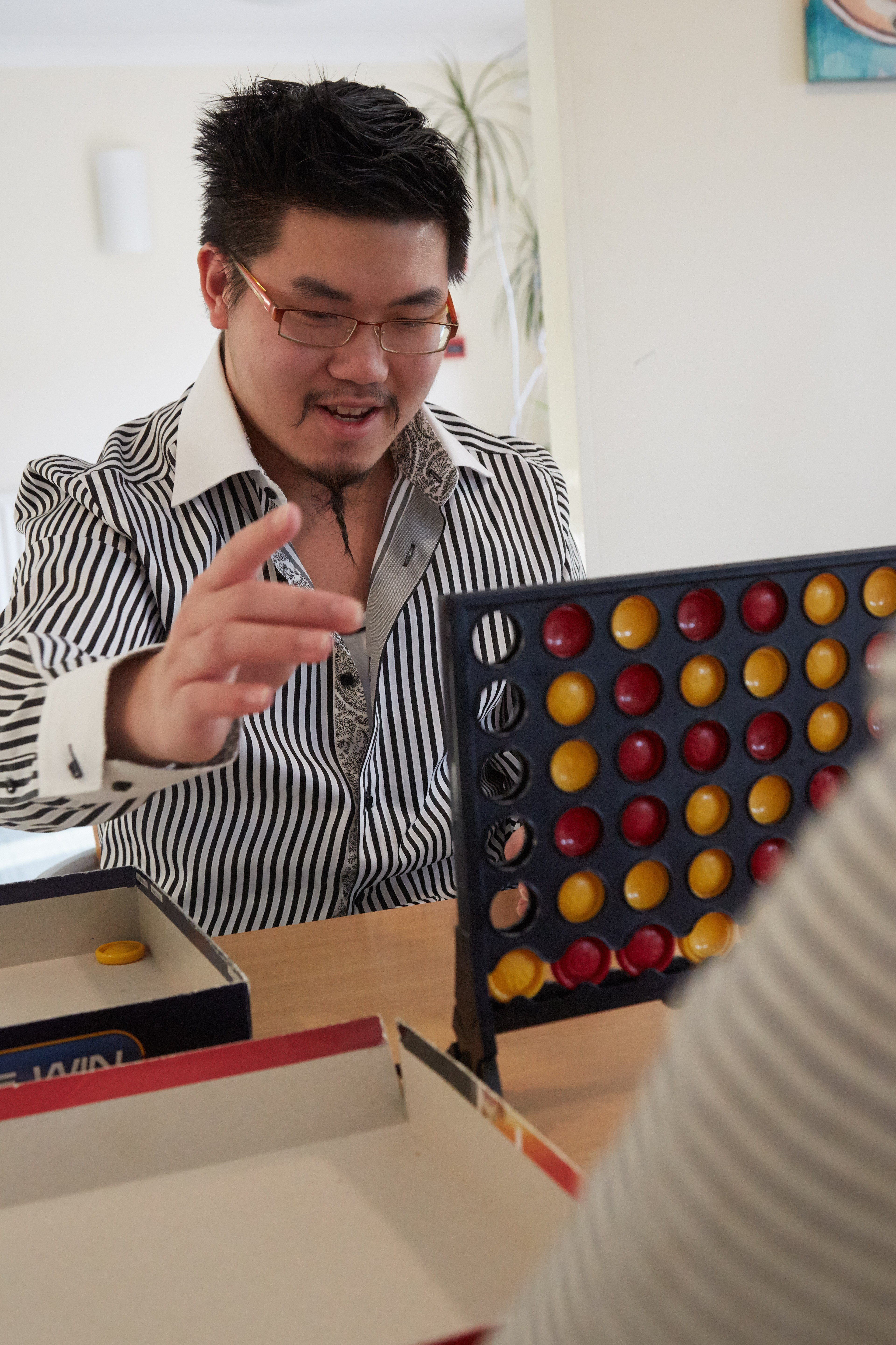 service user playing Connect Four in Daniel Yorath House