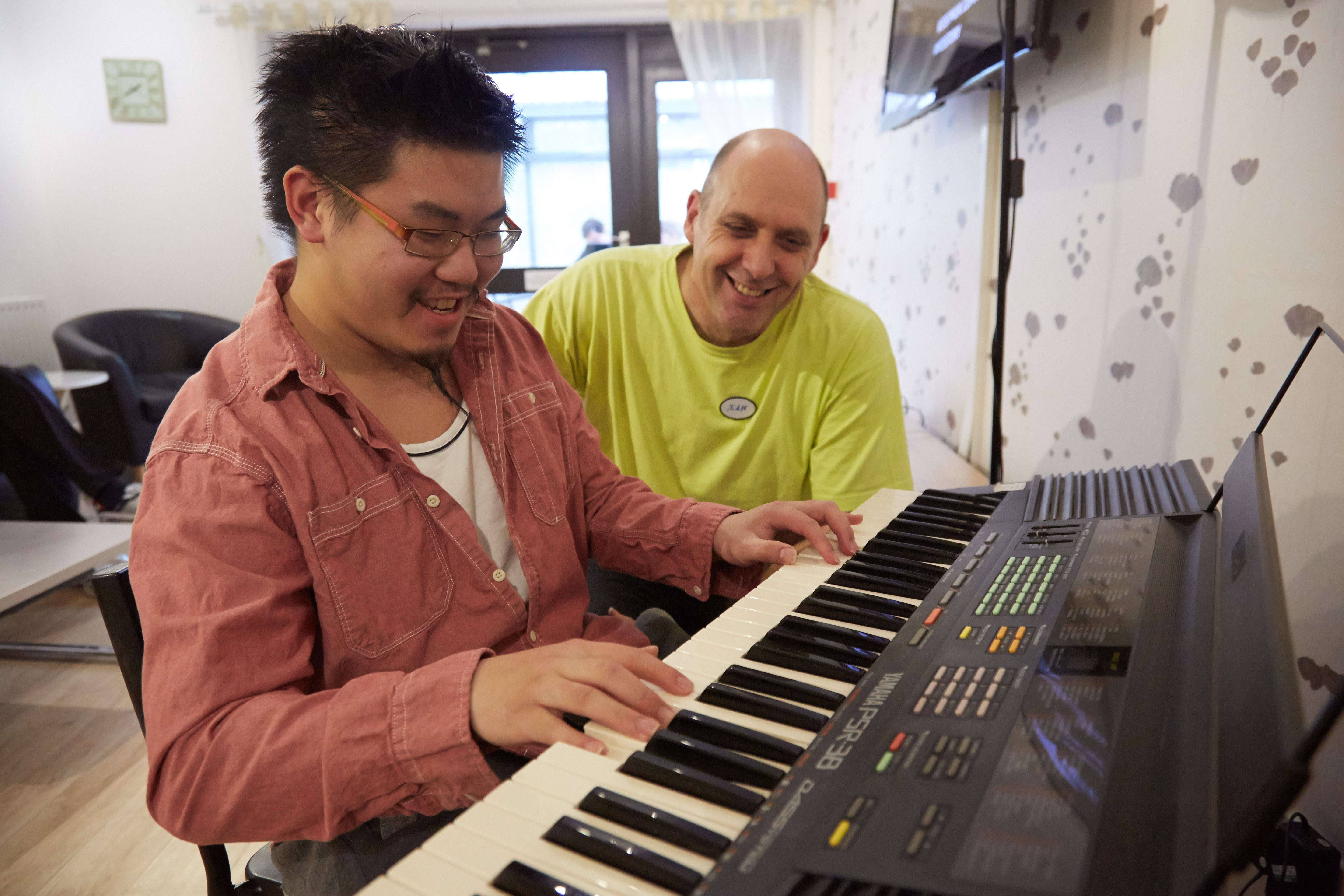 support worker watches a service user playing the piano  in Daniel Yorath House
