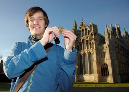 Fen House service user Luke standing outside a cathedral holding a medal