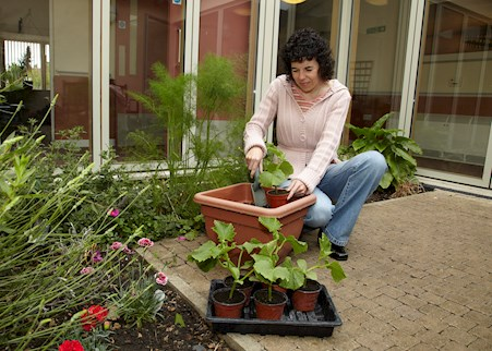 service user working in the garden area of Fen House