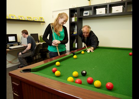 service user playing pool with support worker in the recreation area of Fen House
