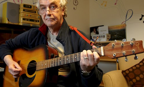 service user playing guitar in the recreation room of Fen House