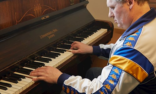 service user playing the piano in the recreation room of Fen House