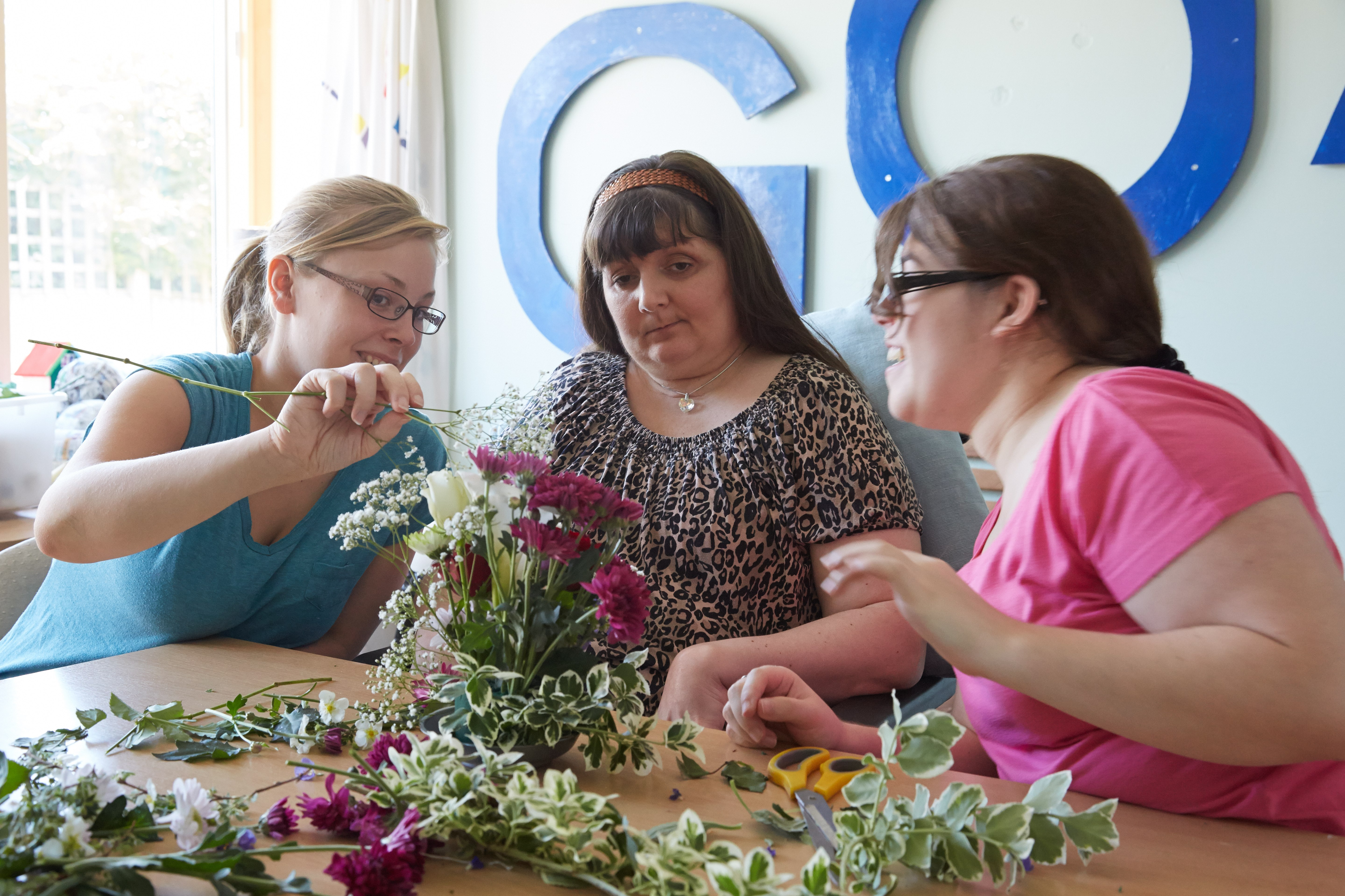 service users flower arranging with support worker in Fen House