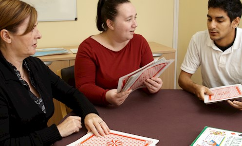 support worker playing cards with service users in Graham Anderson House