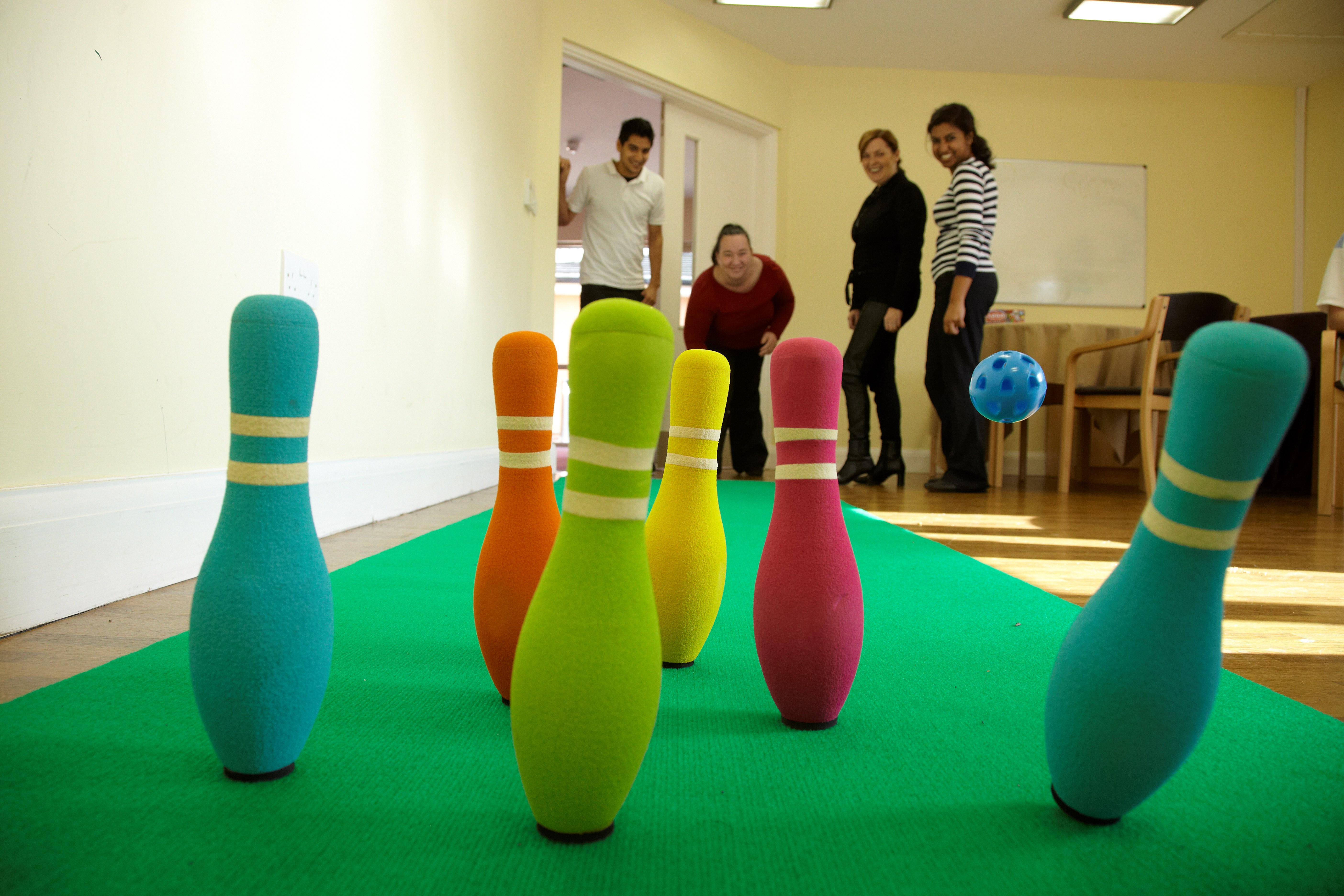 service users and support workers play skittles in Graham Anderson House