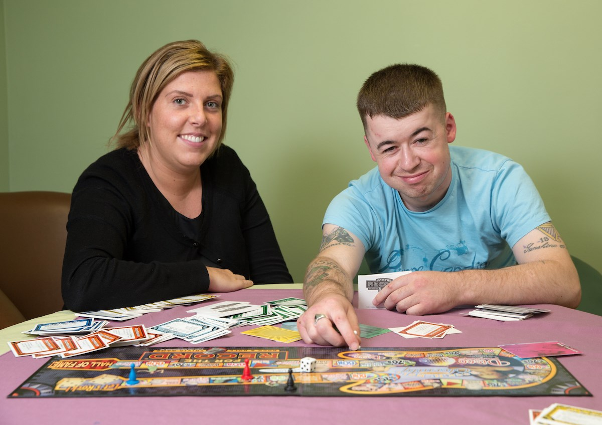 Male service users and female support worker playing in the recreation room at Graham Anderson House