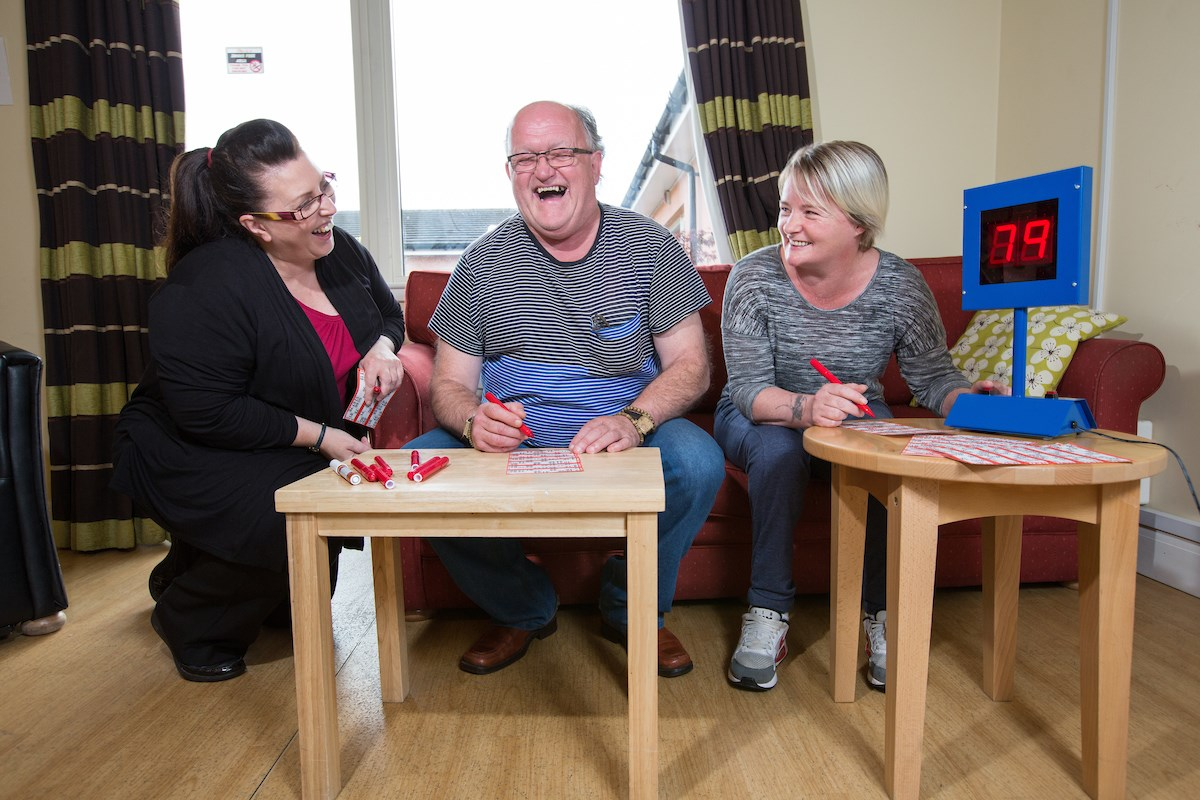 service user and two support workers in the recreation room at Graham Anderson House