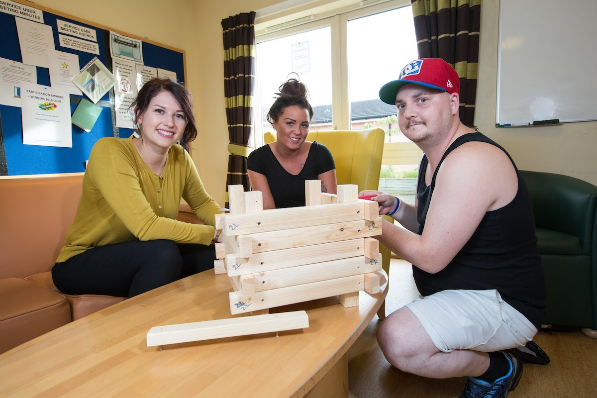 service user and two support workers playing giant jenga in the recreation room at Graham Anderson House