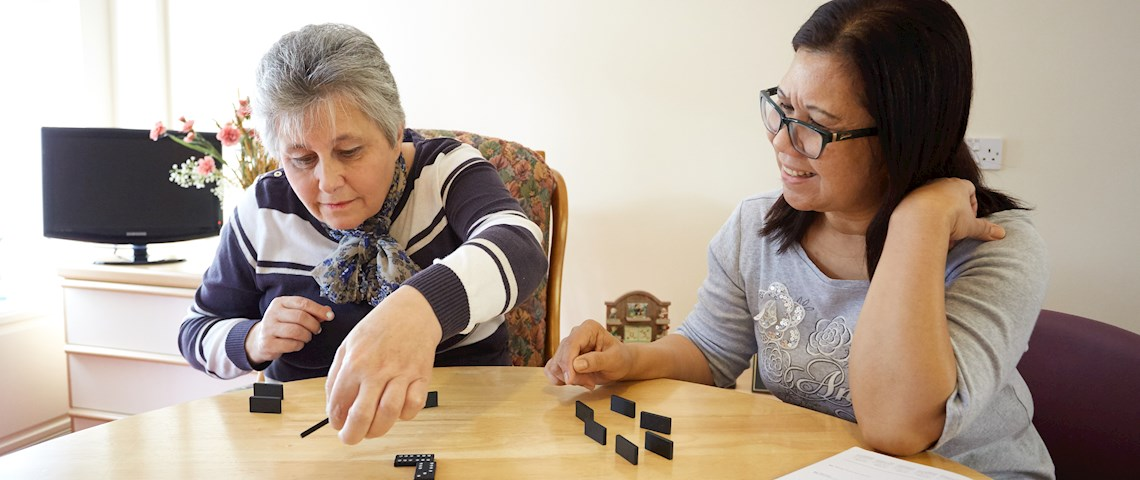 support worker with service user playing domino's in Kent House