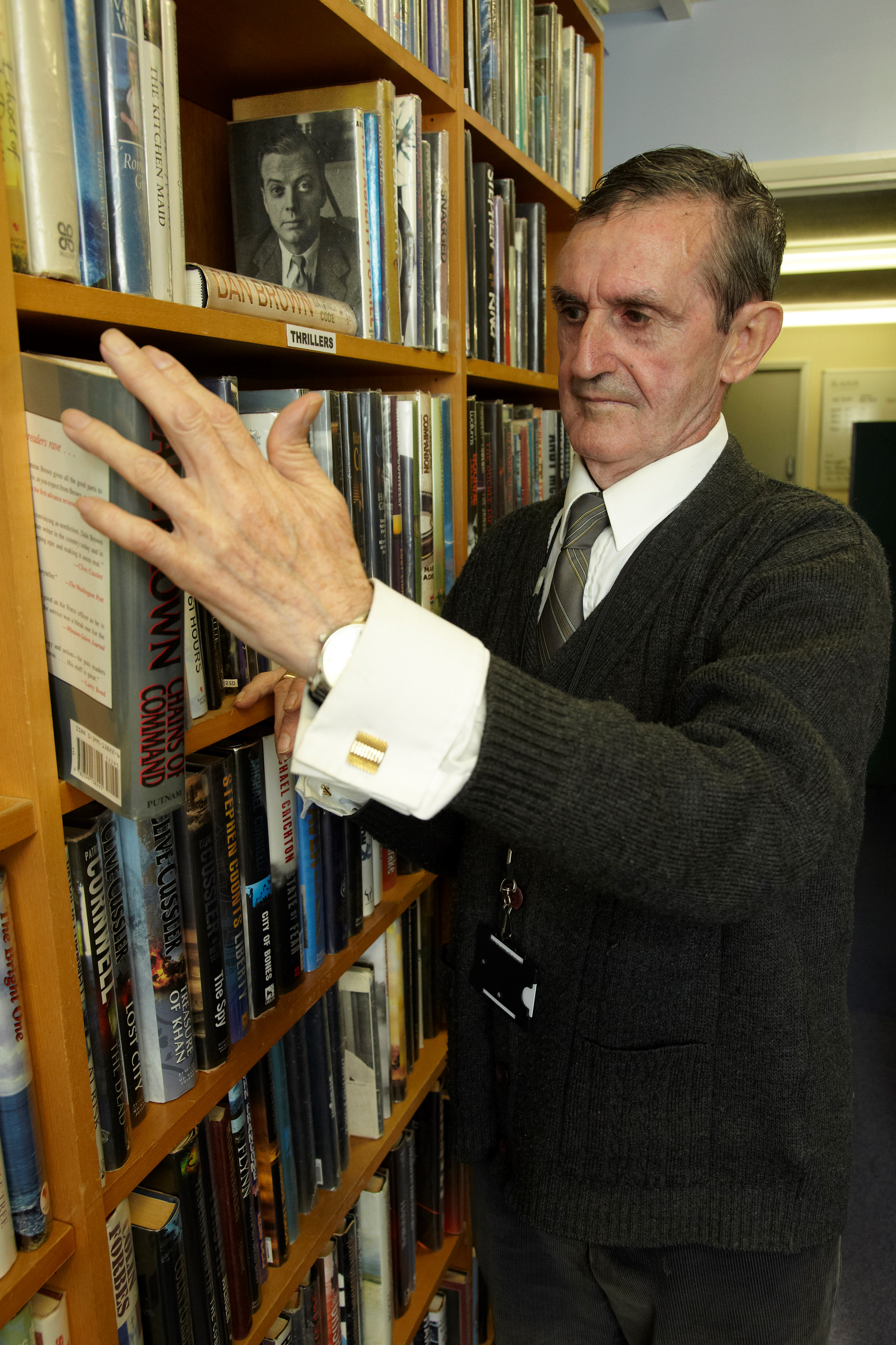 Kent House service user John standing in front of bookshelves in a library