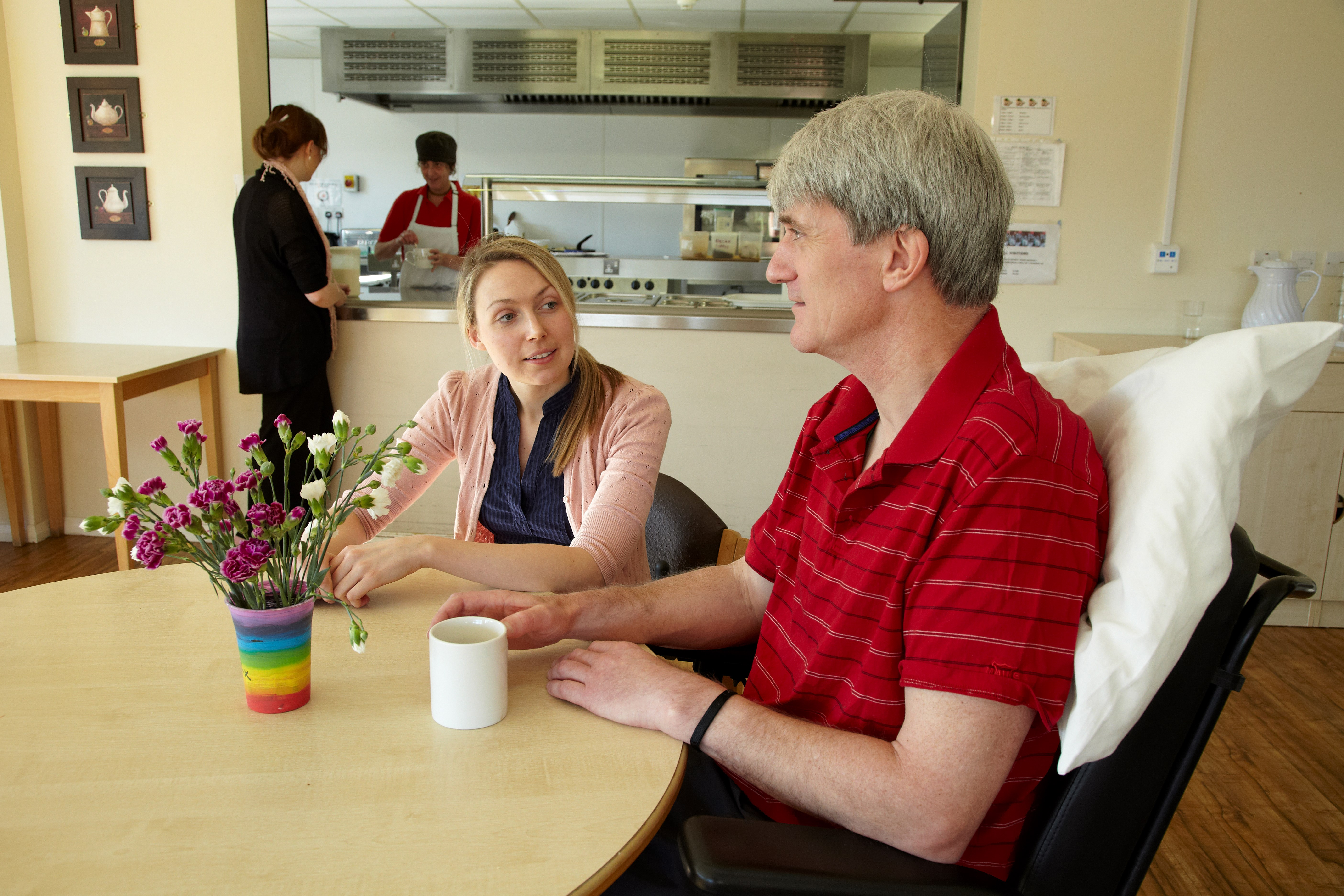 support worker sits with service user in the dining area of Kerwin Court