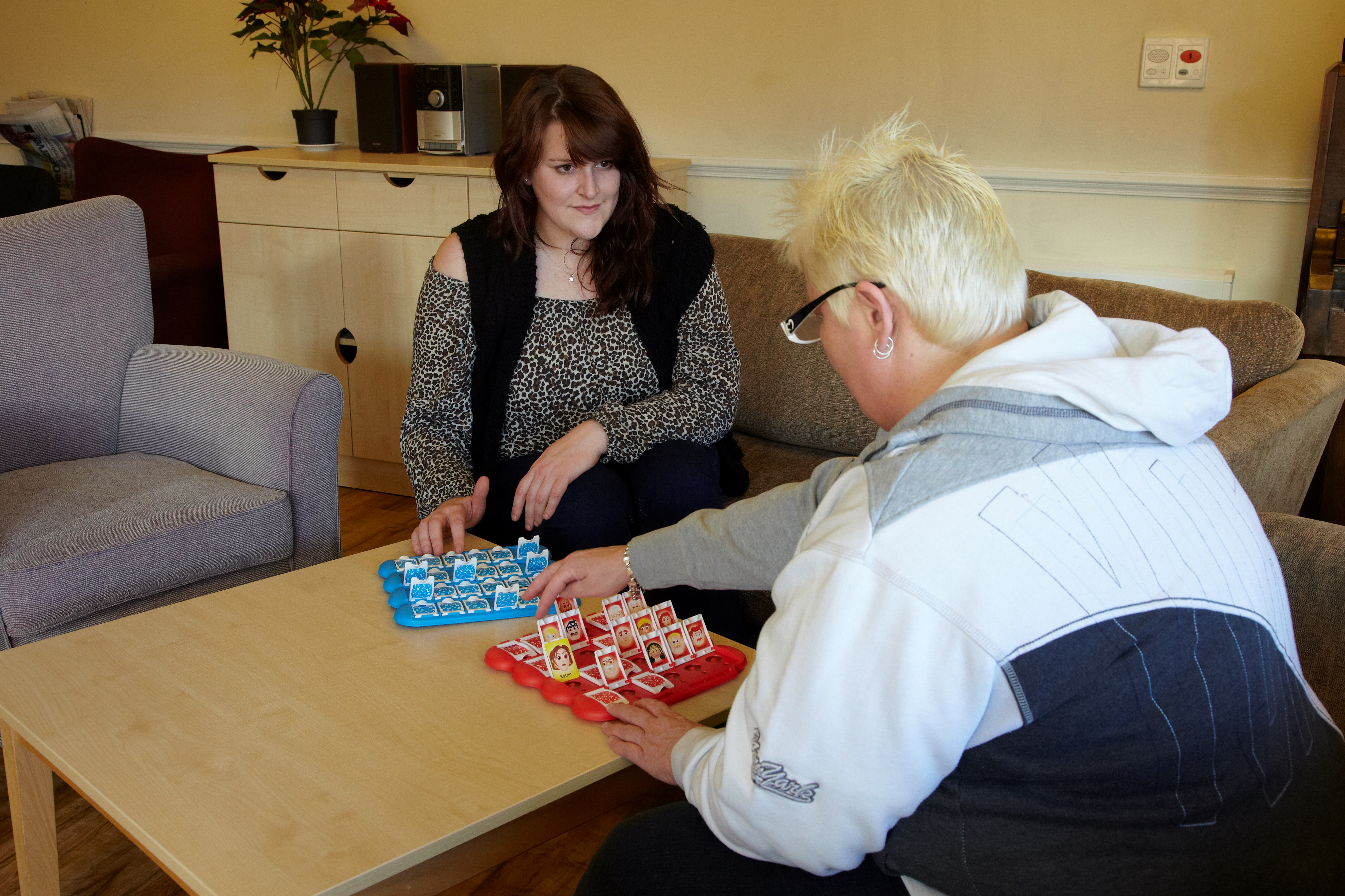 service user playing Guess Who with support worker at Kerwin Court
