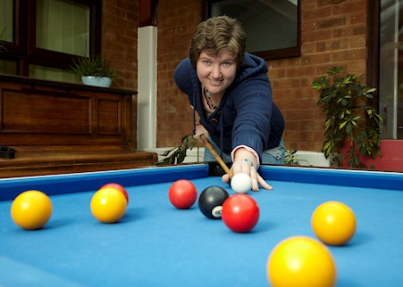 Service user Meg playing pool in the recreation room at TEM House
