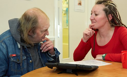 support worker going through paperwork with service user in the therapy rooms of York House