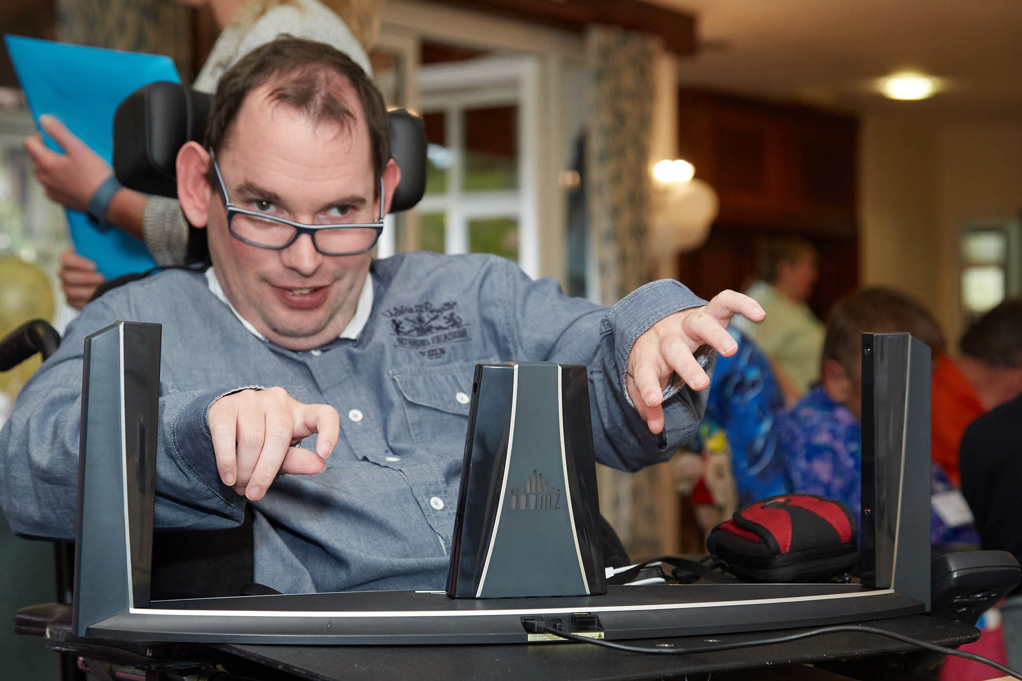 Service user, Will, using assistive technology in Ernest Kleinwort Court