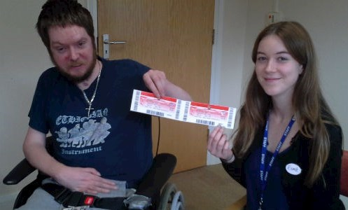Service user poses with Psychology Assistant with complementary tickets to the football