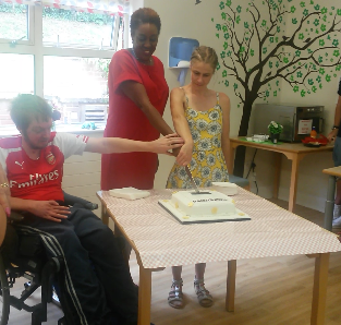 Chief Executive, Irene Sobowale, cutting a cake with service user at The Woodmill