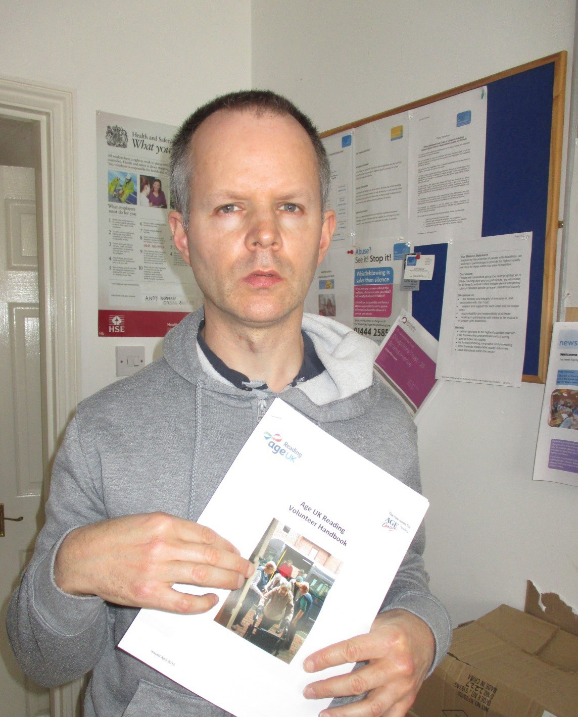 Mark proudly displaying his official status as volunteer with Age Concern