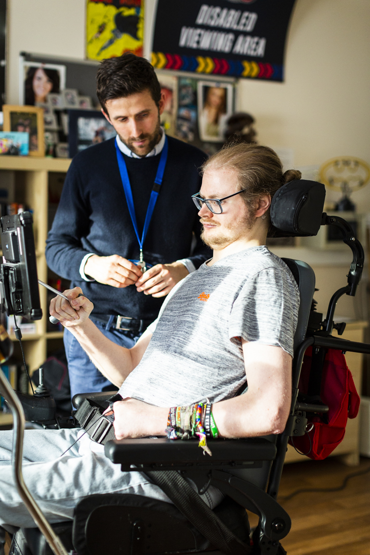 Male service user with assistive technology tablet and a support worker