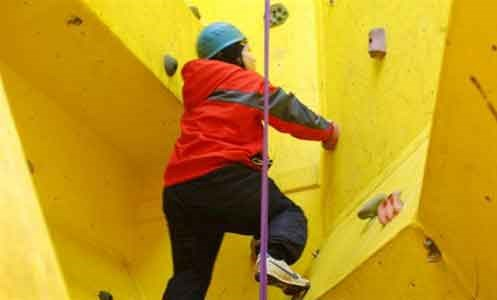 Pupil climbing a wall as part of extra curricula activities at Heathermount School